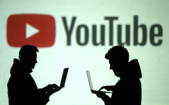 Silhouettes-of-mobile-device-users-are-seen-next-to-a-screen-projection-of-Youtube-logo-in-this-pict[1]